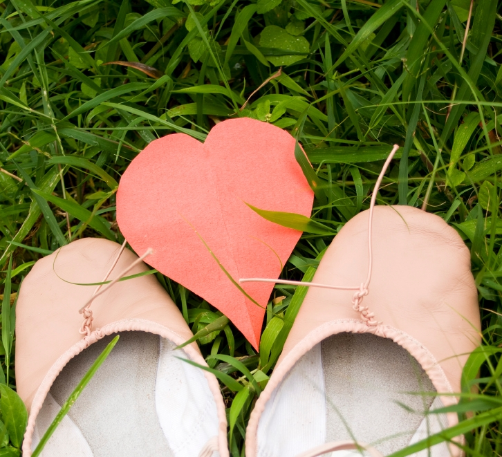 love and ballet; ballet shoes and red heart shape in grass